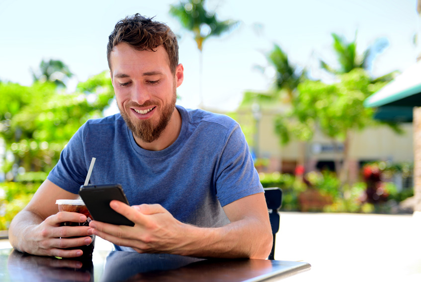 young man holding a smartphone and smiling